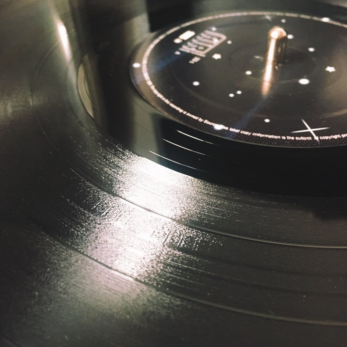 Das Bild zeigt die geriffelte Oberfläche einer schwarzen Schallplatte in Großaufnahme.